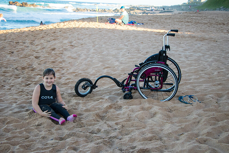 Anika with her Ottobock wheelchair and Freewheel on the beach